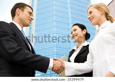 Image of successful partners handshaking at background of modern building - stock photo