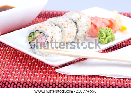 Image of Sushi rolls with sticks and plate - stock photo