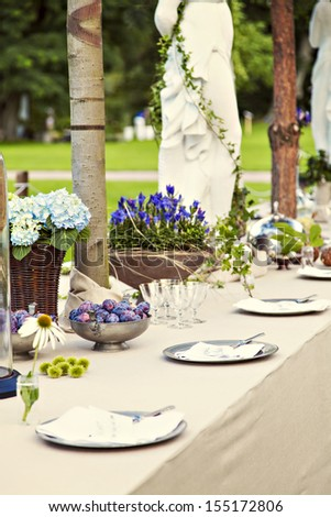 Image of table setting for a rustic wedding or dinner party in the garden. - stock photo
