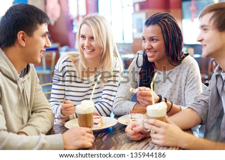 Image of teenage friends chatting while spending time in cafe
