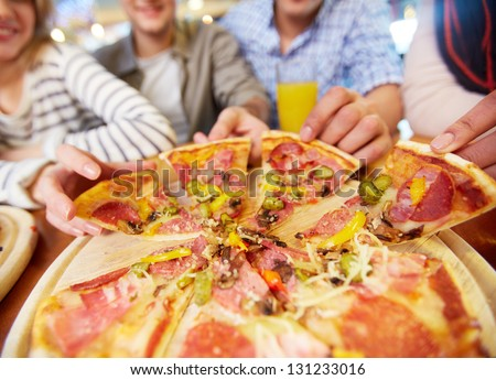 Image of teenage friends hands taking slices of pizza - stock photo
