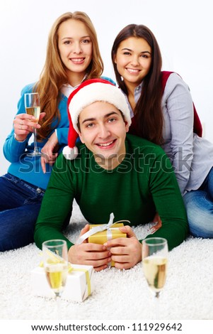 Image of teenage friends with champagne and gifts looking at camera