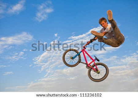 Image of teenager on a bicycle in a jump on a background blue sky.