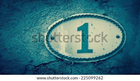 Image of the number 1 (indicating a house number) on weathered stucco wall of antique house. France. Aged photo. - stock photo