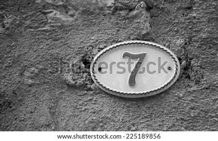 Image of the number 7 (indicating a house number) on weathered stucco wall of antique house. France. Aged photo. Black and white. - stock photo