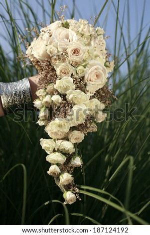 image of the Wedding bouquet of white roses in front of high grass and blue sky , wedding bouquet - stock photo
