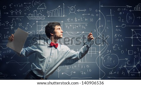 Image of thoughtful male student holding notebook in classroom