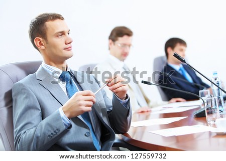 Image of three businesspeople at table at conference
