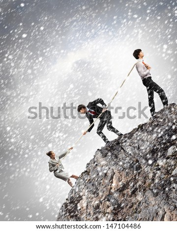 Image of three businesspeople pulling rope atop of mountain under falling snow - stock photo