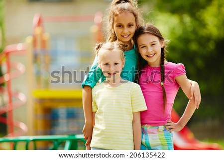 Image of three cute girls looking at camera with smiles outdoors  - stock photo