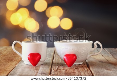 image of tow red heart shape chocolates and couple cups of coffee on wooden table in front of bokeh abstract background. valentine's day celebration concept