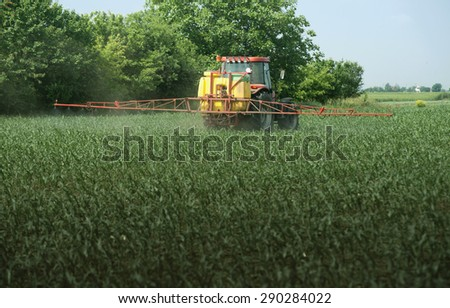 Image of tractor spraying pesticides  - stock photo