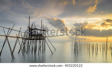 Image of traditional fishermen timber and bamboo jetty known as LANGGAI  during sunset - stock photo