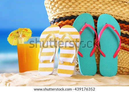 Image of tropical sandy beach, fruit cocktail, straw bag and flip flops. Summer concept