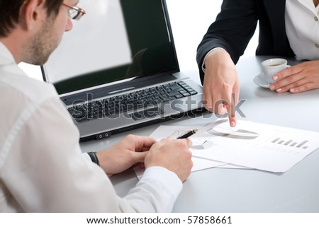 Image of two business partners discussing documents lying on the table - stock photo