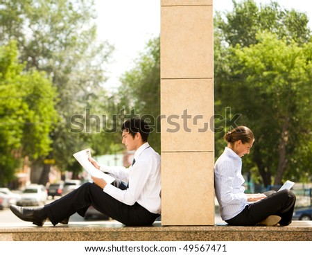 Image of two business partners sitting outside and working - stock photo