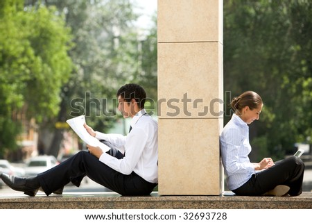 Image of two business partners sitting outside and working with documents - stock photo
