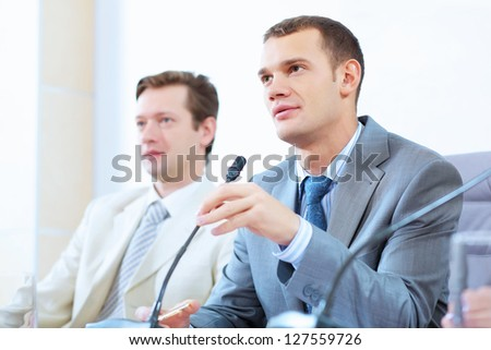 Image of two businessmen sitting at table at conference