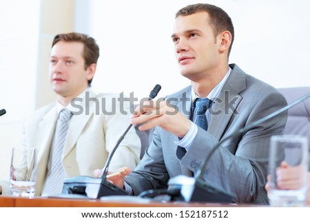 Image of two businessmen sitting at table at conference - stock photo