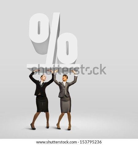 Image of two businesswomen holding percentage symbol above head - stock photo