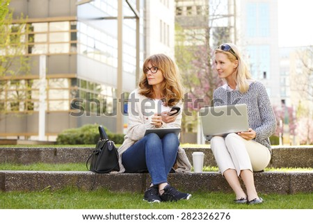 Image of two casual businesswoman sitting in front of office building while using digital tablet and computer. Business people have a coffee break. - stock photo