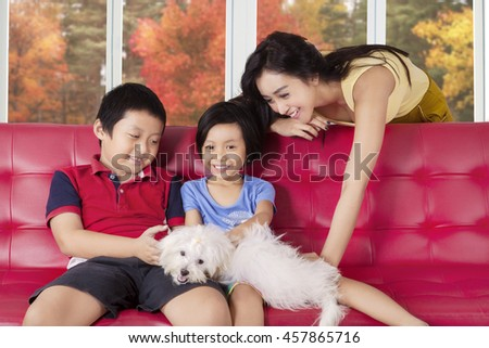 Image of two cheerful children and their mother playing puppy on the sofa at home, shot with autumn background on the window - stock photo