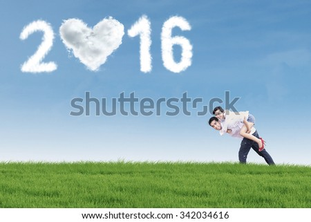 Image of two cheerful young couple having fun on the meadow with clouds shaped numbers 2016 on the sky