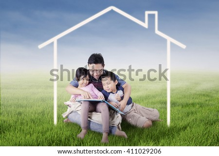 Image of two children and their father sitting on the meadow while reading a book under a house symbol