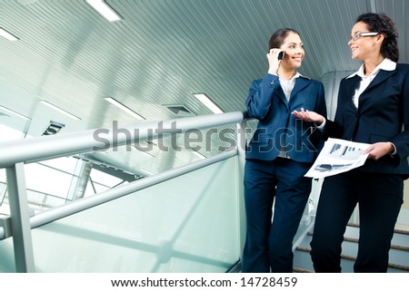 Image of two colleagues discussing new business project while going downstairs in office building - stock photo