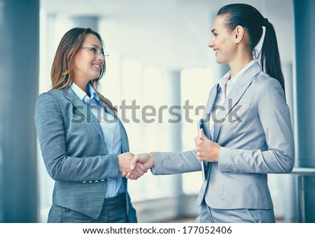 Image of two confident businesswomen handshaking - stock photo