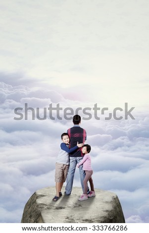Image of two cute children embracing their father while standing on the rock at the mountain peak - stock photo