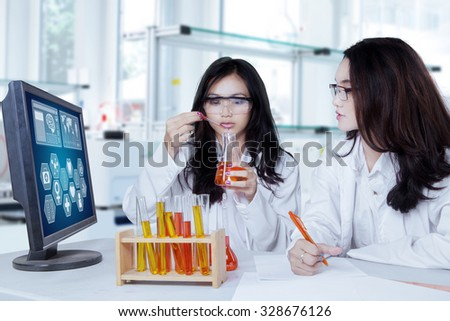 Image of two female student wearing uniform and doing research in the laboratory - stock photo