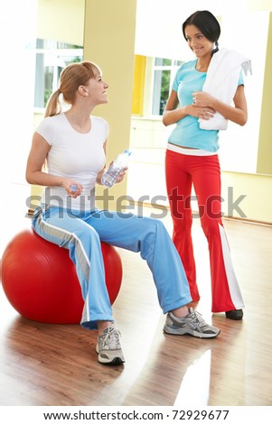 Image of two girls talking and looking at each other in the gym