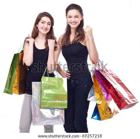 Image of two girls with their purchases. Isolated on white background. - stock photo