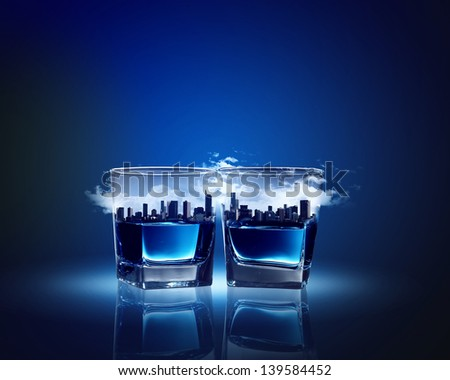 Image of two glasses of blue liquid with city illustration in - stock photo