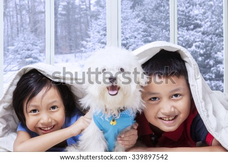 Image of two happy children and their puppy lying under blanket in bedroom with winter background on the window - stock photo