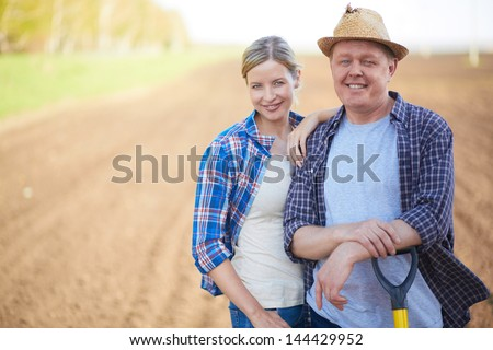 Image of two happy farmers on background of plowed field - stock photo