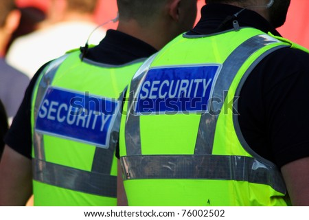 Image of two male security Guards with bright tops on. - stock photo