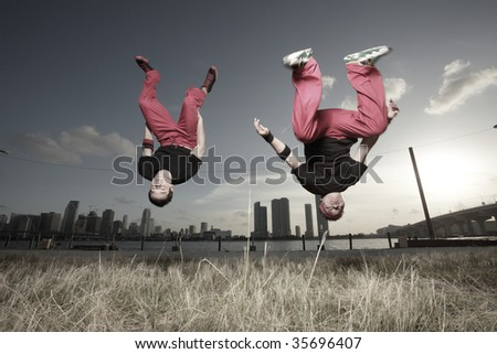 Image of two men performing a midair flip - stock photo