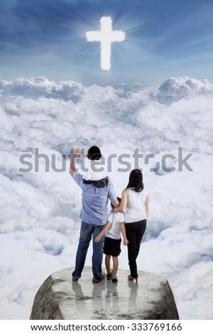 Image of two parents and their children standing on the cliff while looking at a cross sign on the sky - stock photo