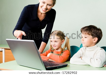 Image of two pupils looking at laptop monitor while teacher pointing at it - stock photo