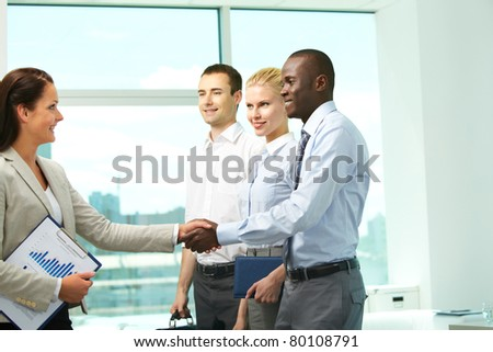 Image of two successful associates handshaking with partners near by - stock photo