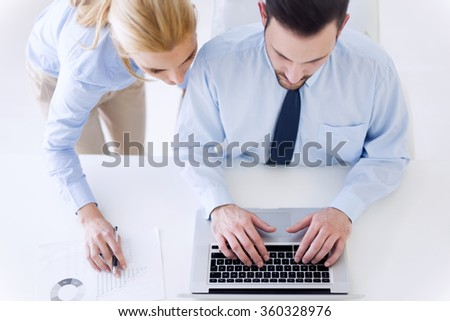 Image of two successful business people working at meeting in office.Top-view of a businessman using his laptop.He is wearing a blue shirt and a black tie. - stock photo