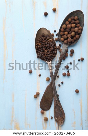 Image of two vintage spoons full of black peppercorn and allspice on rustic wooden cutting board - stock photo