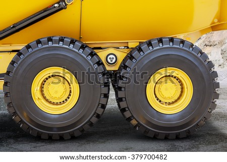 Image of two wheels of mining truck with black tires on the mining site - stock photo