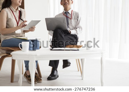 Image of two young business partners using touch pad at meeting - stock photo