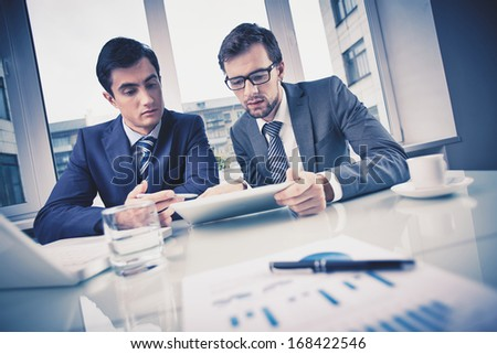 Image of two young businessmen discussing document in touchpad at meeting - stock photo