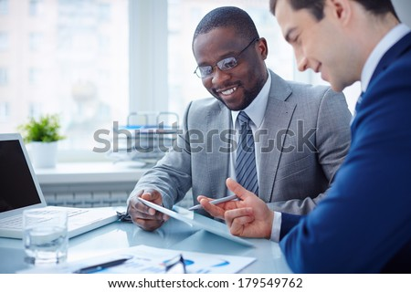 Image of two young businessmen interacting at meeting in office - stock photo