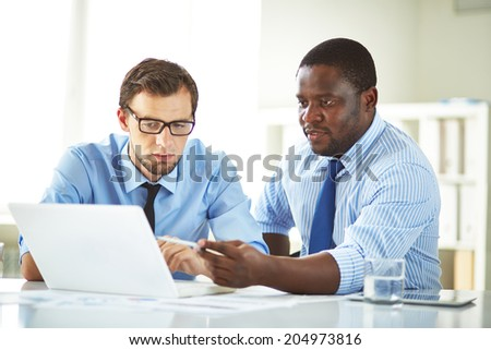 Image of two young businessmen using laptop and interacting at meeting - stock photo