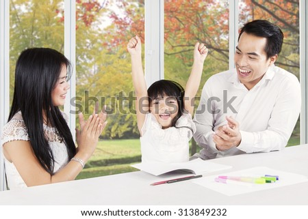 Image of two young hispanic parents giving applause on their child at home after finishing homework - stock photo